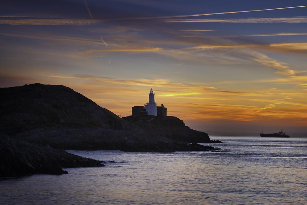 Mumbles Head lighthouse at sunrise from Bracelet Bay, Gower Peninsula